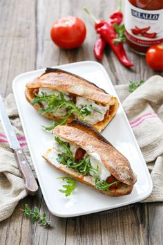 Spicy Italian Meatball Sandwiches with melty fresh mozzarella and baby arugula on top.