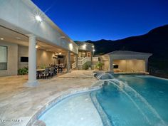 Amazing backyard features an infinity edge pool and spa  covered gazebo complete with outdoor kitchen.