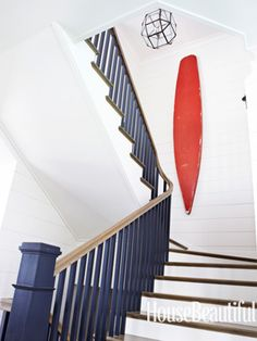 Vintage surfboard in stairwell. Design: Parrish Chilcoat and Joe Lucas. housebeautiful.com. #surfboard #stairs