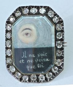 An eye miniature brooch, circa 1800, set gold and silver and in a surround of diamonds. The watercolour on ivory miniature depicts an eye in clouds and beneath it is a most unusual motto and poignant motto : il ne voit et ne veira que toi [he does not see me, he only sees you]. A rare original eye miniature piece.