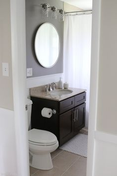 Just a few small tweaks completely updated this bathroom space. Love the DIY shiplap, dark gray walls, and round mirror!