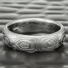 """The exquisite REFLECTIONS pattern is slightly more understated on our domed, 6mm wide band. It follows the Japanese tradition of the """"beauty of nature's imperfection"""", with an organic pattern, which repeats on each quadrant of the ring. The pattern of each REFLECTIONS band is skillfully forged and coaxed out of a solid piece of our patented stainless Damascus steel. It is unrivaled for its intentional design, amazing ergonomics, and superior metals."""