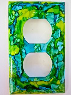 For sale on our PeakdancersArt easy site.  Standard double electric outlet cover by GE decorated with Alcohol Ink