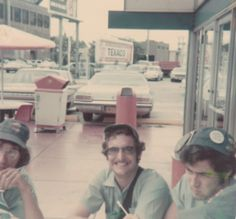 Vendors Evan Pomeroy, unknown, and Ron Pollakov chow down at Franksville on the NW corner of Clark and Addison before work  circa 1974