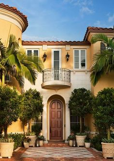 Stunning tropical dream house ... love the yellow ... beautiful palm and potted tree flanked entrance #pinadream
