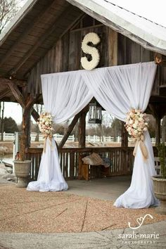 """OK, so obviously not to this extreme. I do like having the drape """"fabric"""" it could even be done with the plastic table runners that you find at party city for supercheap. I have done that before for a party. We would not have to use the expensive flowers for the tiebacks. We could do thick ribbons etc. Maybe instead of the S above, it could be a one and a six that we could make glittered."""