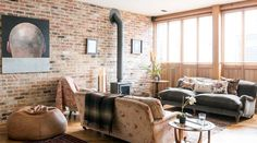 This industrial-style fireplace goes perfectly with the brick wall in this living room in Notting Hill, London