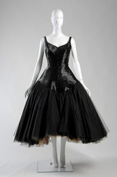 James covered the surface of this 1952 dress with tiny jet bugle beads. The voluminous interior skirt, however, is made from many layers of fine tulle, ranging in color from black to orange to yellow. When the wearer danced or walked, bright flashes of tulle would peep out to flirt with her companions.