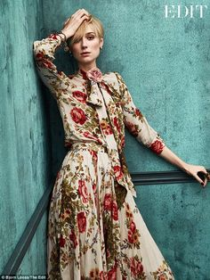 Classy: She leaned against a blue velvet wall while wearing a co-ordinated shirt, skirt and floral brooch all by Gucci