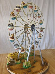 Zebra and giraffe cupcakes on a functional ferris wheel being attacked by a cake lion.
