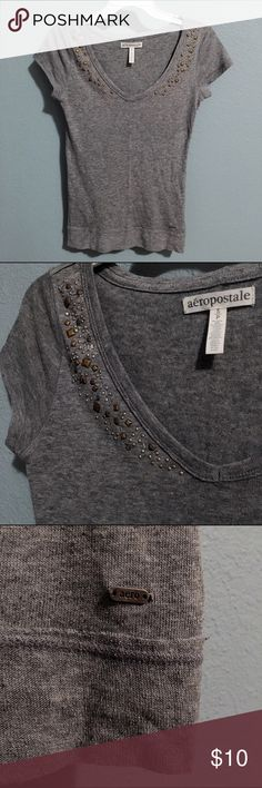 Simple v neck T shirt with bling near chest Grey Aeropostale small v neck stretch shirt. Embellishments near chest, none missing! Aero  logo on bottom left of shirt on metal plate. Aeropostale Tops Tees - Short Sleeve