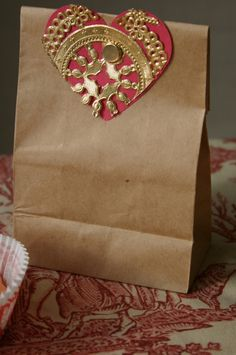 Kraft paper bag and red heart and gold doily