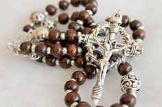 ☧ Catholic Prayer Beads / Religious Jewelry / Handcrafted rosary ☧  This is a beautiful handmade silver and wooden rosary. This piece was handmade using crowd of thorns crucifix and a beautiful Holy Family centerpiece. Great as a gift for men, women, and children or for yourself.  *** ✞ ***  This rosary has Wooden beads (53 beads, 8mm) and 4 10mm silver finish filagree beads. Measures: 5 Decades Total length is 16 Inch Crucifix is 2.5 inches tall  *** ✞ ***  Your item will be ready ...