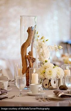 love how naturally elegant this centerpiece looks with the driftwood and candles in glass cylinders.