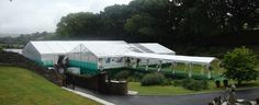 Large marquee wedding built onto scaffolding to accommodate sloping ground.  Walkway leads into a clear roof reception marquee which ajoins a dining marquee looking out onto the river Avon, Devon.  Beautiful!