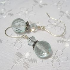 Gorgeous faceted Aqua Glass Quartz rounds are capped with detailed Bali sterling silver beads, topped with lovely Light Azore Swarovski crystals. Suspended on hand-formed sterling ear wires. Measures 1 1/2 inches in length from top of ear wire to bottom of bead. These are promptly made to order and quickly shipped.