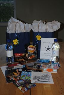 Out Of Town Bags (Picture Heavy) :this is what I was envisioning except with a cute reusable tote. Waters, snax, emergency items, and a newsletter.
