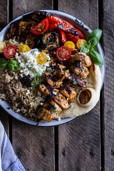 Everything about this dish is amazing -- chicken souvlaki and rice pilaf with marinated veggies and feta tzatziki