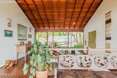 Janelas de vidro com vista para a natureza e móveis rústicos, como o banco de madeira decoram a casa de praia em Ilhabela.
