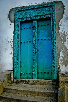embellished aquamarine door set into a wall of cracked and faded white stucco