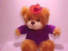 Western Red Hat Bear - Red Hat Society Ladies.  Western Red Hat bear wears a purple shirt, red beads and sports a western hat with a purple flower.  13 inch bear is 10 inches tall when sitting.  Found only at http://www.myredhatstore.com/Western-Red-Hat-Bear-Myredhatstorecom-exclusive-FE1653.htm