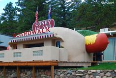 """Coney Island Colorado (commonly The Coney Island) in Bailey, Colorado is a 1950's diner shaped like a giant hot dog, with toppings. The building has been called """"the best example of roadside architecture in the state"""""""