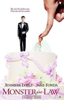 A wedding cake with figurines of the bride and groom. A finger pushes the bride into the cake.