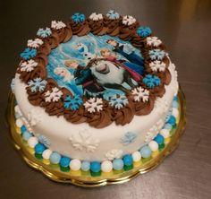 Dětský dort na motivy pohádky Ledové království, obalený bílým fondánem, dozdobený vločkami a obrázkem z jedlého papíru.