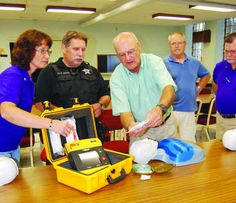 Paul Kuss (third from right) Whiting emergency medical service coordinator points out features an automated external defibrillator members Whiting Lions Club, which donated the device to the department.