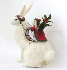 "This is the largest piece I've made to date, standing 16"" high.   It will also be the last hare I make for some time. Although very near and  dear to my heart, my sketch book has some new creatures that I am excited  to begin work on.  The Hare is entirely needle felted from 100% wool roving and has a wire  armature. His saddle is made from an antique tatted lace doily and wool  felt.   The Holly Faerie is hand stitched from natural fibres (with the exception  of her win..."