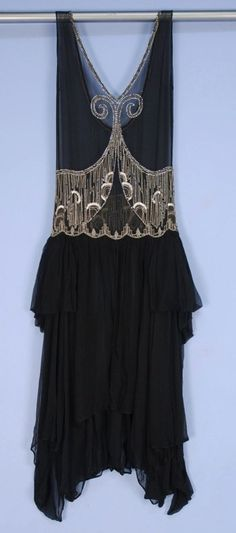 DECO BEADED CHIFFON OVER-DRESS, 1920's. Black silk with V-neck and U-back, having rhinestone and silver beaded neckline, front scrolls and midriff band, full skirt split at center front, eneven hem folded into side panniers. Front