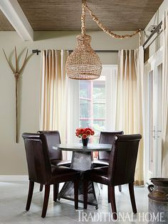 Earthy neutrals prevail in the area surrounding the game table; a cool chandelier dangles overhead. - Photo: Werner Straube / Design: Erik Kolacz