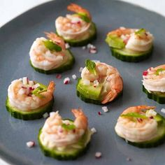 thin-cucumber-slices-topped-with-prawns-and-peppered-with-chopped-radish-and-small-green-leaves-appetizers-for-a-crowd-on-a-serving-plate