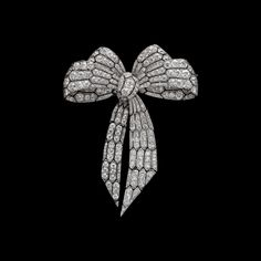 Traditional Diamond Bow Brooch. Platinum millegrain and diamond bow brooch knot brooch, the ribbon patterned with elongated hexagons tied into four loops, fastened at the central cluster and falling down below, terminating in sharp angles.