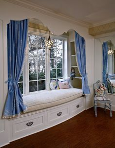 How sweet! An old fashioned wooden cornice with pretty tied back panels. Blue & white is a classic too.