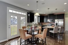Suede orange and gray chairs with natural lighting and stainless steel appliances.The Rosecliff II model at Maple Valley Estates by Dan Ryan Builders. Home Style Ideas