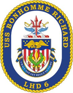 The USS Bonhomme Richard's ship crest.  Dark blue and gold are the colors traditionally used by the United States Navy. The red, white, and blue shield reflects the national colors of the USA and suggests its coat of arms. The six red stripes represent the ship's hull number as well as the six coins placed beneath the mast during mast stepping; red being the color of valor and sacrifice. The gold fleur-de-lis highlights the heritage of the first ship named Bonhomme Richard. The wreath of two…