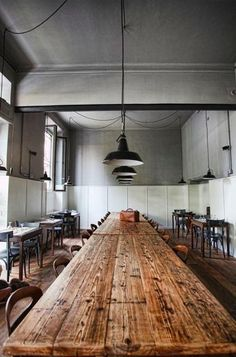 U Barba Long wooden communal tables encourage family-style dining; source similar barn-like pendants from Barn Light Electric