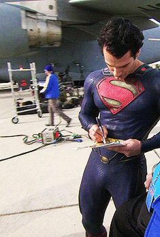 Henry Cavill signing autographs between takes on Man of Steel set.