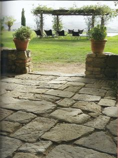 Rustic Italian stone patio, planters and vine covered arbor