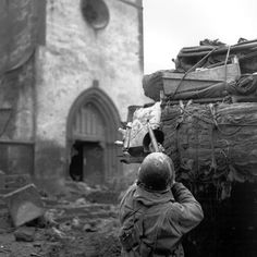American soldiers from B-68th Armored Infantry Battalion engage German snipers in a Church at Oberhoffen, while the tank provides supporting fire. February, 1945.