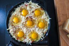 Μια απολαυστική συνταγή με ψητά αυγά, τυρί και κρεμμύδια για ένα πλούσιο θρεπτικό πρωινό ή ακόμα και ως κανονικό γεύμα.    Συστατικά    3 κουταλιές της σούπας βούτυρο  2 μεγάλα κρεμμύδια, λεπτοκομμένα  1/4 της κούπας λιαστές ντομάτες ψιλοκομμένες  1 κούπα τριμμένη φρυγανιά  3/4