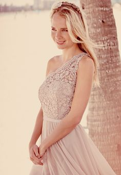 Feminine and chic, this figure-flattering mesh bridesmaid dress gets topped off with an illusion corded lace one shoulder neckline. Style F15711 from David's Bridal.