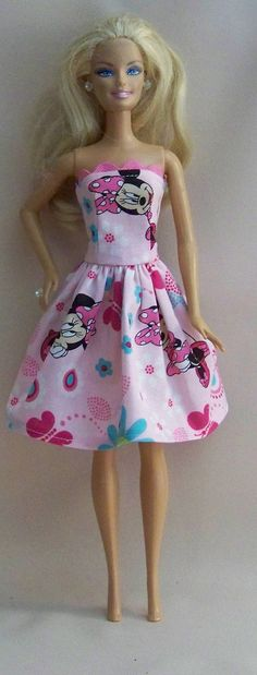 Handmade Barbie dress is a pink Minnie Mouse cotton print. The dress is trimmed with pink rick rack at the bodice top. The back closure is velcro. This dress will fit the newer Barbies with the belly button. Dress only-doll is not included. I have a pet and smoke free home. Thank you for looking.