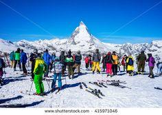 ZERMATT, SWITZERLAND -APRIL 14, 2016: Skiers prepare to ski at  Gornergrat train station with Matterhorn peak in background, a summit station above Zermatt in Switzerland. - stock photo