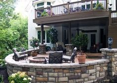 Love this combo of small upper deck, covered lower space and rock look walls/ patio ! EverGrain - Weathered Wood Deck with powder-coated aluminum under deck ceiling system, Stone veneered sitting walls, Stamped/Stained/Sealed concrete patio, Moonlight Decks post lights, Wall lighting, retaining wall, landscaping and a natural stone patio in Leawood, KS.