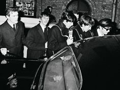 Early February 1964. Neil Aspinall escorts The Beatles to a waiting limo in Paris.