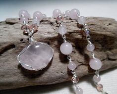 Rose Quartz and Swarovski Crystal Necklace 18 long in silver.   This beautiful One of a Kind Necklace features a Genuine Rose Quartz Gemstone that has been wire wrapped with silver wire to create a pendant. The Rose Quartz itself is an oval shape that measures 20mm x 25mm and hangs from a handmade 18 chain. The chain is made by individually wire wrapping Genuine Rose Quartz beads and Vintage Rose Swarovski Crystals. Each bead and crystal is then wire wrapped to each other to create a chain…