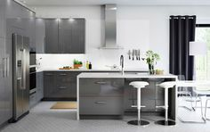 A large kitchen with grey high-gloss drawers, doors and a kitchen island.