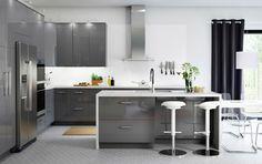 Vaste cuisine à portes et façades de tiroir en gris ultrabrillant, et îlot de cuisine